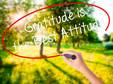 Woman Hand Writing Gratitude is the Best Attitude on blank transparent board with a marker isolated over green field background. Business concept. Stock Photo