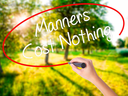Woman Hand Writing Manners Cost Nothing on blank transparent board with a marker isolated over green field background. Business concept. Stock Photo Stock Photo