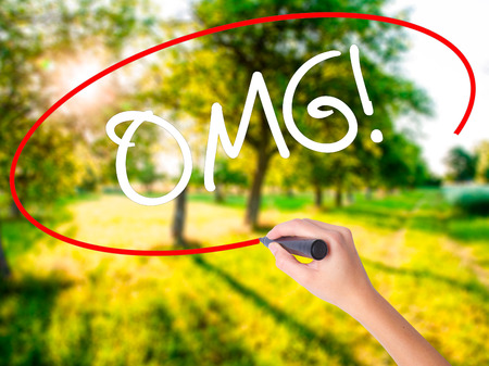 gosh: Woman Hand Writing OMG (Oh My God) on blank transparent board with a marker isolated over green field background. Business concept. Stock Photo Stock Photo