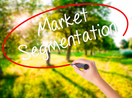 Woman Hand Writing Market Segmentation on blank transparent board with a marker isolated over green field background. Stock Photo Stock Photo