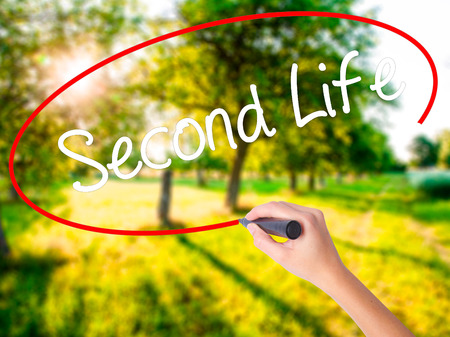 Woman Hand Writing Second Life on blank transparent board with a marker isolated over green field background. Stock Photo