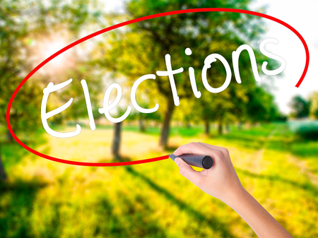 Woman Hand Writing Elections on blank transparent board with a marker isolated over green field background. Business concept. Stock Photo