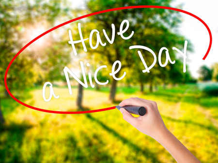 Woman Hand Writing Have a Nice Day with a marker over transparent board . Isolated on green field. Live, technology, internet concept. Stock Photo Stock Photo