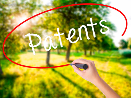 patents: Woman Hand Writing Patents on blank transparent board with a marker isolated over green field background. Stock Photo Stock Photo