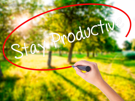 stay in green: Woman Hand Writing Stay Productive on blank transparent board with a marker isolated over green field background. Business concept. Stock Photo Stock Photo