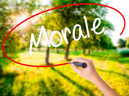 morale: Woman Hand Writing Morale on blank transparent board with a marker isolated over green field background. Business concept. Stock Photo