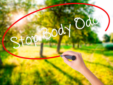 Woman Hand Writing Stop Body Odor on blank transparent board with a marker isolated over green field background. Stock Photo