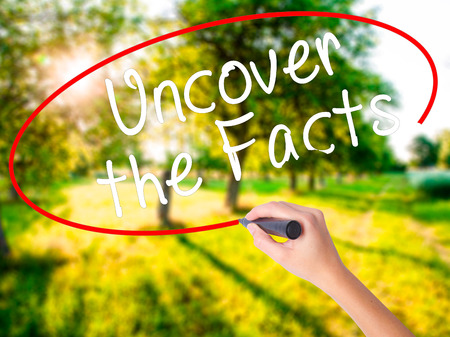 uncover: Woman Hand Writing Uncover the Facts on blank transparent board with a marker isolated over green field background. Business concept. Stock Photo