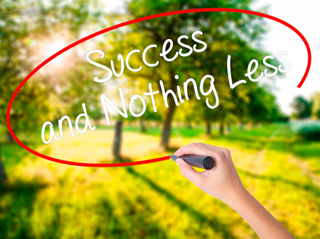 work less: Woman Hand Writing Success and Nothing Less on blank transparent board with a marker isolated over green field background. Business concept. Stock Photo