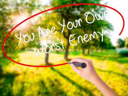 the worst: Woman Hand Writing You Are Your Own Worst Enemy on blank transparent board with a marker isolated over green field background. Stock Photo Stock Photo