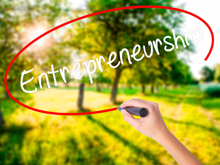 Woman Hand Writing Entrepreneurship on blank transparent board with a marker isolated over green field background. Business concept. Stock Photo Stock Photo