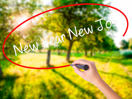 Woman Hand Writing New Year New Job on blank transparent board with a marker isolated over green field background. Business concept. Stock Photo Stock Photo