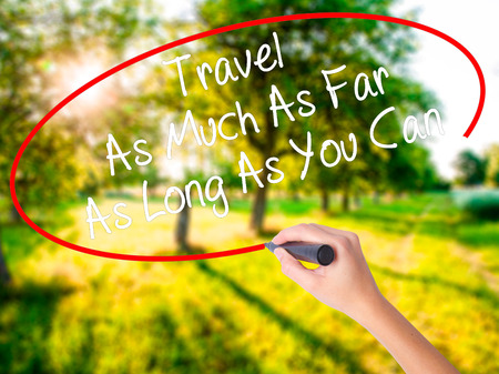 Woman Hand Writing Travel As Much As Far As Long As You Can  on blank transparent board with a marker isolated over green field background. Business concept. Stock Photo