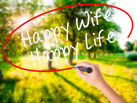Woman Hand Writing Happy Wife Happy Life on blank transparent board with a marker isolated over green field background. Business concept. Stock Photo Stock Photo