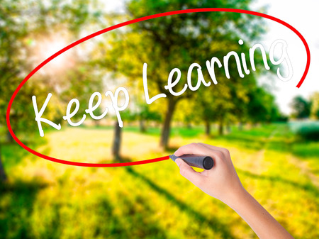 Woman Hand Writing Keep Learning on blank transparent board with a marker isolated over green field background. Business concept. Stock Photo