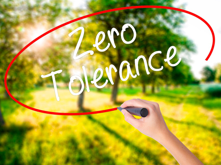 tolerancia: Woman Hand Writing Zero Tolerance on blank transparent board with a marker isolated over green field background. Stock Photo Foto de archivo