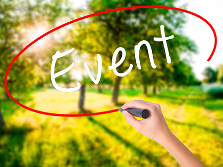 Woman Hand Writing Event on blank transparent board with a marker isolated over green field background. Business concept. Stock Photo Stock Photo