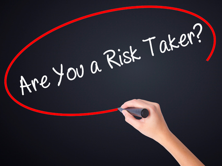 taker: Woman Hand Writing Are You a Risk Taker? on blank transparent board with a marker isolated over black background. Business concept. Stock Photo Stock Photo