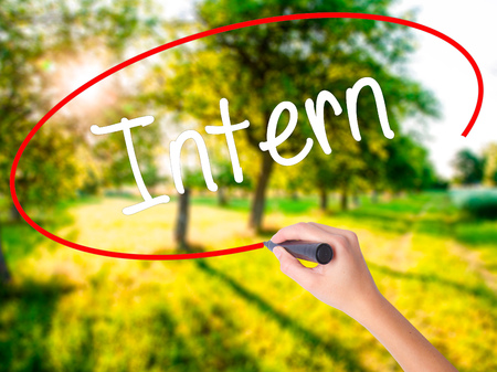 Woman Hand Writing Intern  on blank transparent board with a marker isolated over green field background. Stock Photo Stock Photo