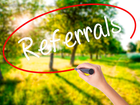 Woman Hand Writing Referrals on blank transparent board with a marker isolated over green field background. Stock Photo