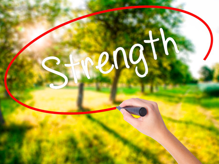 firmeza: Woman Hand Writing Strength on blank transparent board with a marker isolated over green field background. Business concept. Stock Photo