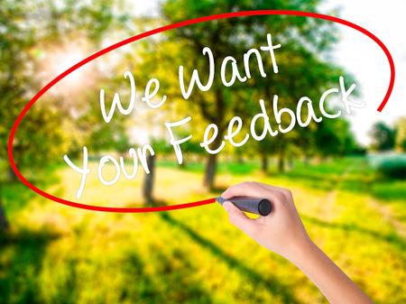opinions: Woman Hand Writing We Want Your Feedback on blank transparent board with a marker isolated over green field background. Business concept. Stock Photo Stock Photo
