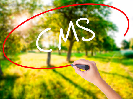 Woman Hand Writing CMS (Custom Management System) on blank transparent board with a marker isolated over green field background. Stock Photo Stock Photo