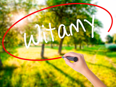 Woman Hand Writing Witamy (Welcome in Polish) on blank transparent board with a marker isolated over green field background. Stock Photo