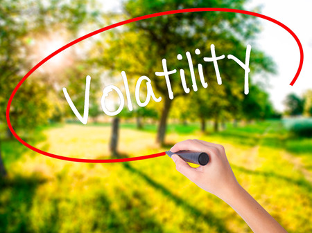 volatility: Woman Hand Writing Volatility on blank transparent board with a marker isolated over green field background. Business concept. Stock Photo