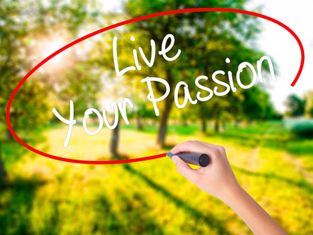 Woman Hand Writing  Live Your Passion on blank transparent board with a marker isolated over green field background. Business concept. Stock Photo