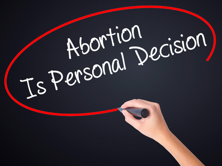 abortion womb: Woman Hand Writing Abortion Is Personal Decision on blank transparent board with a marker isolated over black background. Business concept. Stock Photo Stock Photo