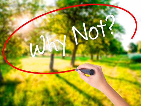 Woman Hand Writing Why Not? on blank transparent board with a marker isolated over green field background. Business concept. Stock Photo