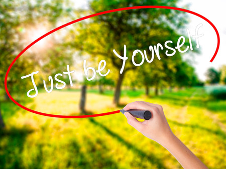 Woman Hand Writing Just be Yourself on blank transparent board with a marker isolated over green field background. Stock Photo