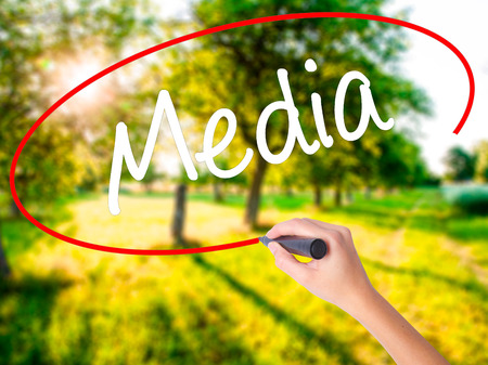 Woman Hand Writing Media on blank transparent board with a marker isolated over green field background. Stock Photo