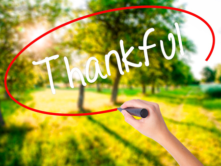 obliged: Woman Hand Writing Thankful  on blank transparent board with a marker isolated over green field background. Stock Photo