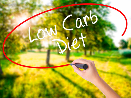 Woman Hand Writing Low Carb Diet on blank transparent board with a marker isolated over green field background. Business concept. Stock Photo Stock Photo