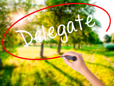 delegado: Woman Hand Writing Delegate on blank transparent board with a marker isolated over green field background. Business concept. Stock Photo