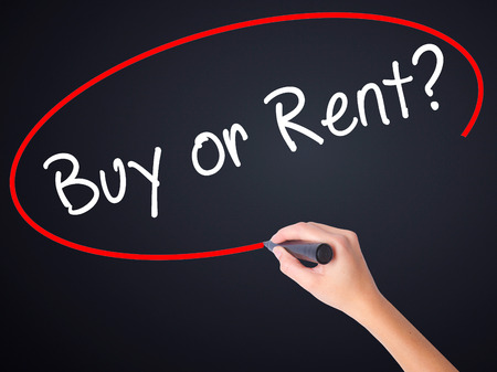 Woman Hand Writing Buy or Rent? on blank transparent board with a marker isolated over black background. Business concept. Stock Photo