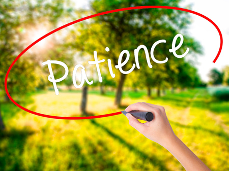 paciencia: Woman Hand Writing Patience on blank transparent board with a marker isolated over green field background. Stock Photo