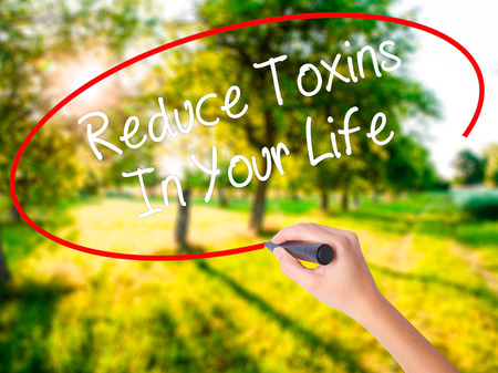 toxins: Woman Hand Writing Reduce Toxins In Your Life on blank transparent board with a marker isolated over green field background. Business concept. Stock Photo