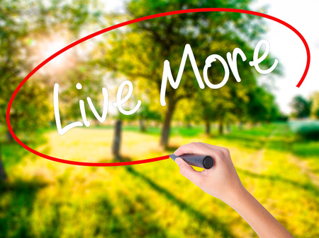 longevity: Woman Hand Writing Live More on blank transparent board with a marker isolated over green field background. Stock Photo