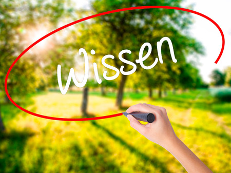 Woman Hand Writing Wissen (Know in German)  on blank transparent board with a marker isolated over green field background. Stock Photo Stock Photo