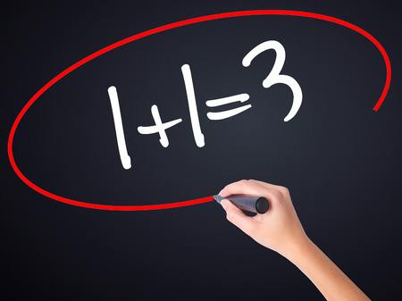 Kobieta piśmie strony 1 + 1 = 3 na pustej tablicy przezroczystą markerem odizolowane na czarnym tle. Zdjęcie Seryjne