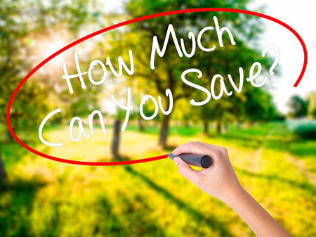 mortgaging: Woman Hand Writing How Much Can You Save? on blank transparent board with a marker isolated over green field background. Business concept. Stock Photo