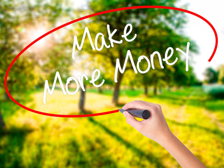 Woman Hand Writing Make Money Money  on blank transparent board with a marker isolated over green field background. Stock Photo