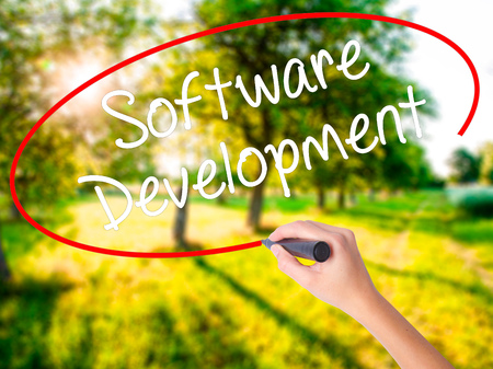 Woman Hand Writing Software Development on blank transparent board with a marker isolated over green field background. Stock Photo