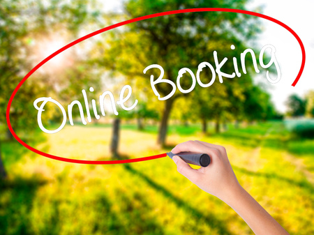 technology transaction: Woman Hand Writing  Online Booking  on blank transparent board with a marker isolated over green field background. Business concept. Stock Photo Stock Photo