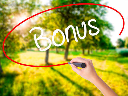 Woman Hand Writing Bonus on blank transparent board with a marker isolated over green field background. Stock Photo