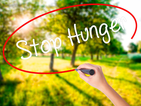 malnutrition: Woman Hand Writing  Stop Hunger on blank transparent board with a marker isolated over green field background. Stock Photo