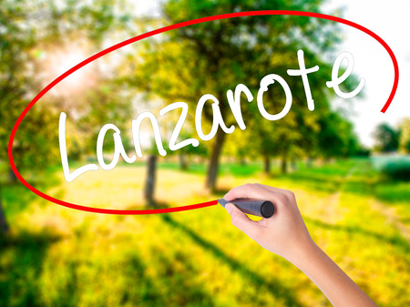 Woman Hand Writing Lanzarote on blank transparent board with a marker isolated over green field background. Stock Photo Stock Photo
